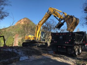 State contractors use an excavator to help remove debris caused by the Woolsey Fire from a property in the Seminole Springs Mobile Home Park earlier this year