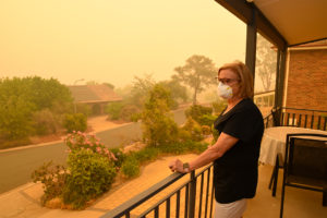 A woman, on a balcony, wears a face mask to protect herself against very dangerous level of air pollution created by nearby wildfires