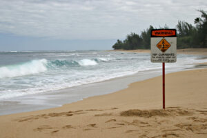 """A sandy tropical beach with Rip Currents Sign and a breaking ocean wave in the background. Sign says: """"Rip Currents - You could be swept out and drown - If in doubt, don't go out""""."""