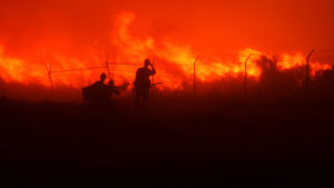 sillouette of two firemen fighting fire
